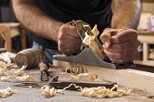 picture of carpenter  - carpenter working with plane on wooden background - JPG