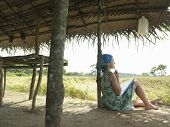 Side view of a female tourist in dress sitting under hut roof in field