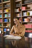 image of shelving unit  - Portrait of a smiling young woman with book at desk in library - JPG