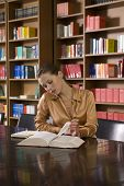 pic of shelving unit  - Beautiful young woman reading book at desk in library - JPG