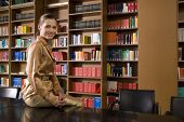 stock photo of shelving unit  - Portrait of a smiling young woman sitting on desk in library - JPG