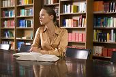 stock photo of shelving unit  - Young woman with book sitting at desk in library - JPG