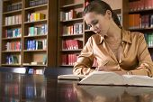 image of shelving unit  - Beautiful young woman studying at desk in library - JPG