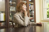 foto of shelving unit  - Side view of a middle aged woman sitting at study table in living room - JPG