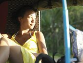 picture of rickshaw  - Young mixed race woman sitting in rickshaw and looking away - JPG