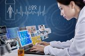 stock photo of x-ray fish  - Busy female doctor typing on laptop looking at digital pictures on blue background - JPG