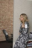 picture of shelving unit  - Side view of a thoughtful young woman leaning against bookcase with mug in office - JPG
