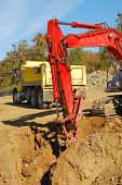 image of track-hoe  - Large track hoe excavator filling a dump truck at a new commercial construction site - JPG
