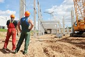 stock photo of labourer  - two builder workers at construction site during concrete pole and beam installation - JPG