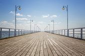 stock photo of old bridge  - Old empty wooden pier over the sea shore with copy space - JPG