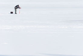 pic of ice fishing  - The fisherman drills a hole in an ice - JPG