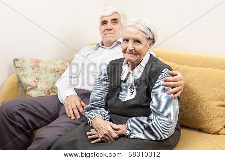 Mature man and senior woman sitting on sofa