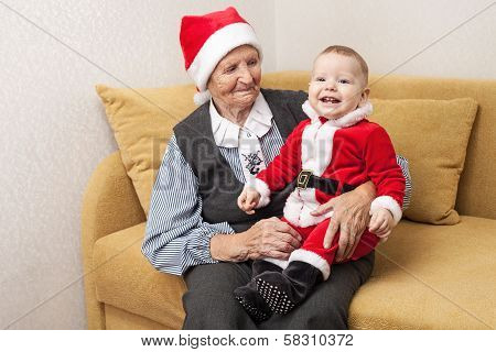 Baby boy in Santa costume with his grandmother