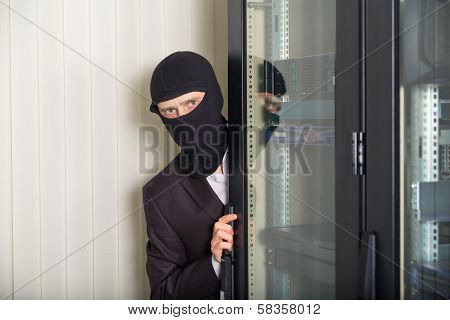 robber in black mask hack server room downloading data on laptop