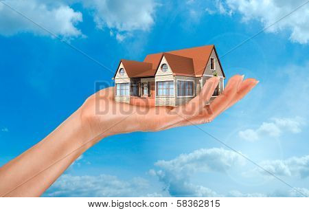 a woman's hand holding a house