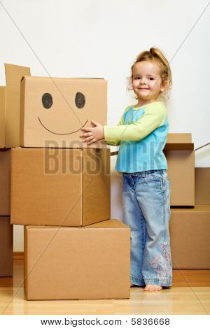 Little Girl With Lots Of Cardboard Boxes Grimacing