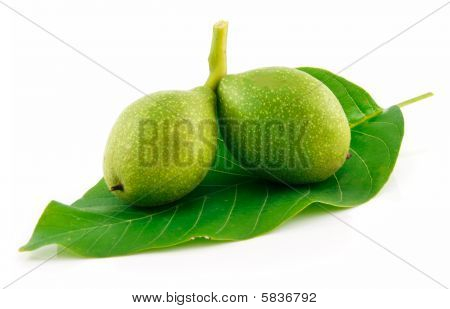 Ripe Broken Walnuts With Green Leaves Isolated On White