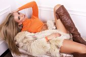sexy woman with blond hair in fur coat lying on sofa