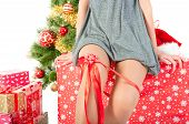 stock photo of bow-legged  - womans sexy legs and red bow near  christmas tree and gift boxes