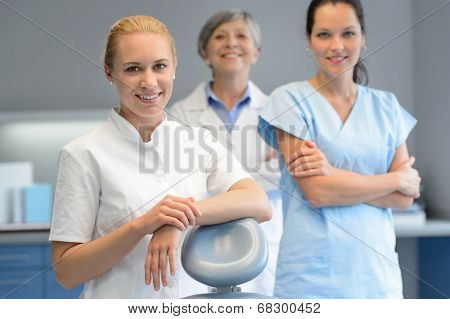Three professional dentist woman team standing dental surgery  looking camera