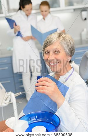 Elderly woman patient dentist team sitting chair at dental surgery