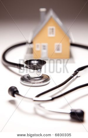 Stethoscope And Model House On Gradated Background