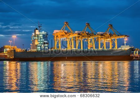 Container Cargo Freight Ship With Working Container Crane In Shipyard At Dusk