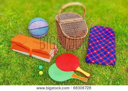 Picnic Basket,  Blanket,  Racquetball And Ball In The Grass