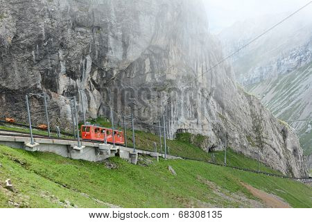 ALPNACHSTAD, SWITZERLAND - July 3, 2014: The Pilatus-Bahn, the world's steepest cogwheel railway nears the top of Mount Pilatus as it emerges from the clouds.