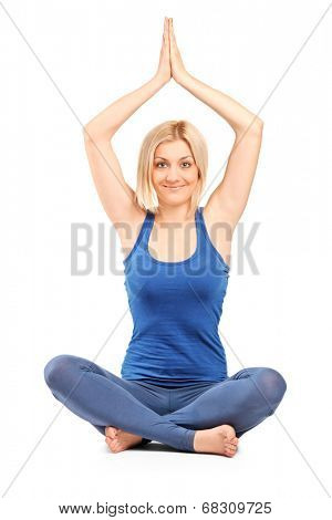 Beautiful girl practicing yoga seated on the floor isolated on white background