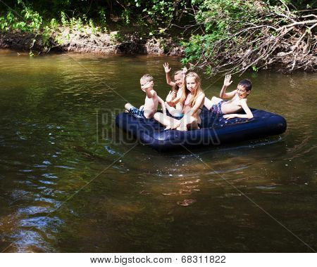 Children floating on the river on an inflatable mattress. Kids, summer, adventure