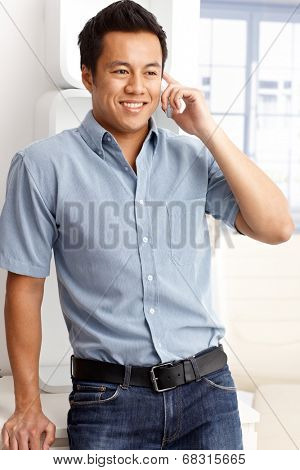 Young man talking on mobilephone, smiling happy, looking away.