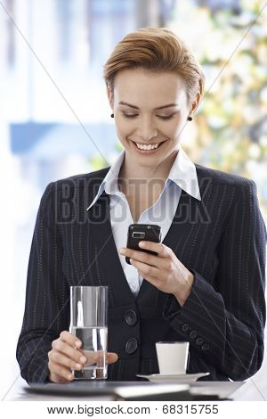 Happy blonde businesswoman using mobilephone, having coffee-break, smiling.