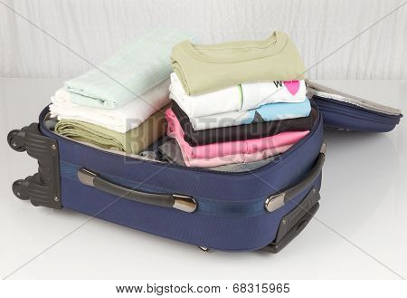 opened suitcase packed with a lot of colorful cloths