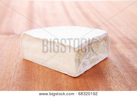 fresh aged french gouda cheese on wooden table