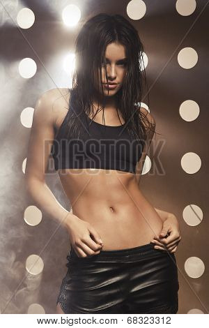 Sexy Sporty Woman With Slim Stomach Over Background With Holes And Smoke