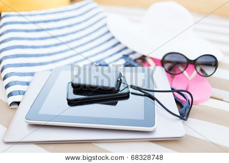 beach, summer, vacation and technology concept - close up of tablet pc computer, smartphone, camera and summer accessories on beach