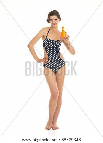Full Length Portrait Of Happy Young Woman In Swimsuit Showing Bottle Of Sun Block Creme