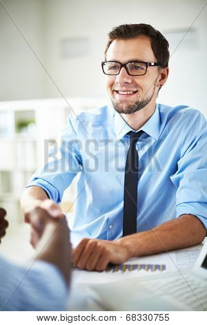 Smiling businessman handshaking with partner after negotiations