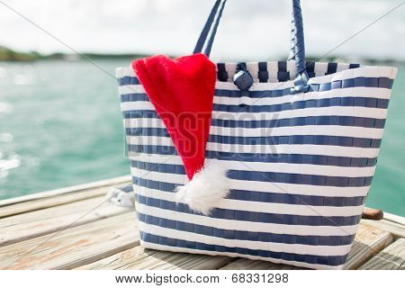 beach, summer, vacation, christmas and accessories concept - close up of beach bag and santa helper hat on wooden pier