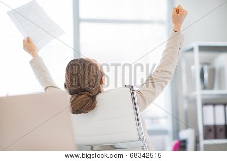 Happy Business Woman With Document Rejoicing At Work. Rear View
