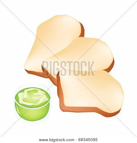 Cut Loaf Of Bread With Cup Of Coconut Cream