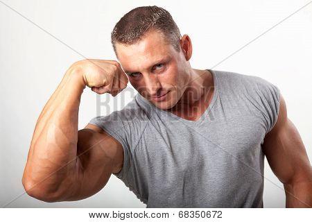 Muscular Man Flexing His Biceps On White