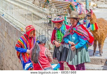 CUZCO, PERU, MAY 1, 2014 - Woman with children, all in traditional attire, bringing a llama to the center of the city. They earn money posing for tourists.