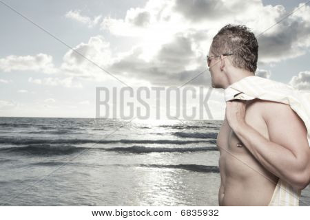 Handsome shirtless man on the beach