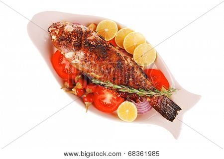 Whole fried sunfish on plate with lemons and peppers.