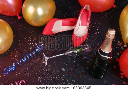 Shoes with confetti, champagne and balloons on the floor