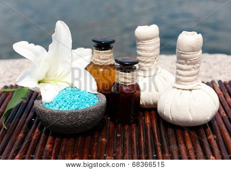 Herbal remedies for massage on bamboo mat, outdoor