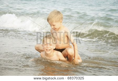 Happy twin children enjoying summer day on a beach