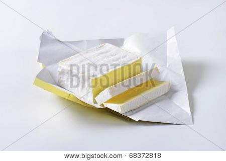 sliced block of cow's milk cheese in a wrapper